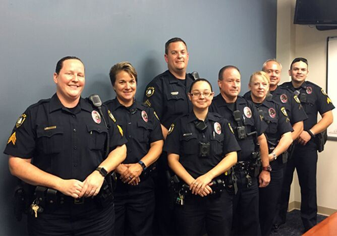 Officers wearing pink badges.